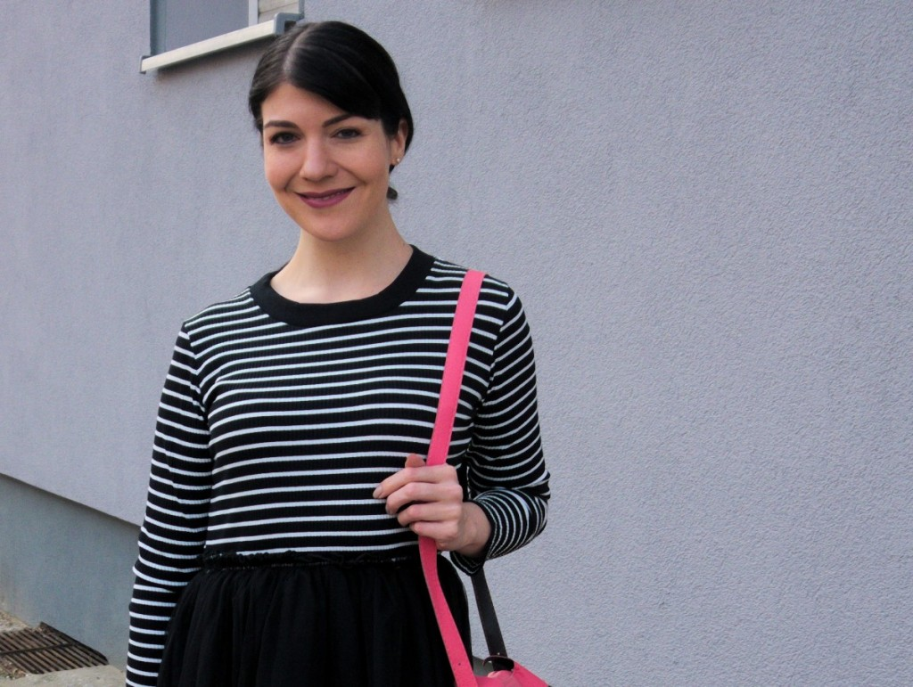 brunette_wearing_striped_pinup_dress_with_tulle_skirt_and_cute_pink_fox_bag_in_Berlin_street