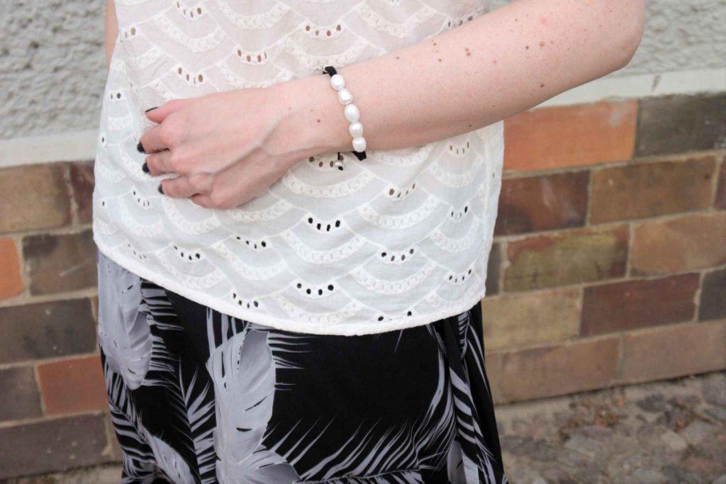 of shoulder blouse and pearl bracelet