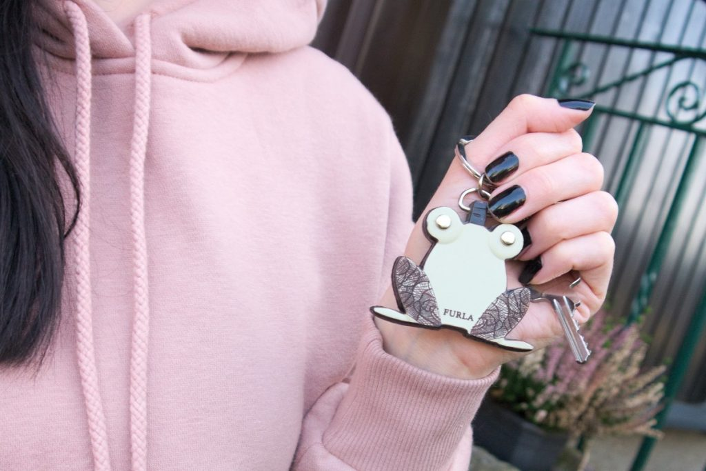 light pink athleisure spring outfit with furla frog keyring