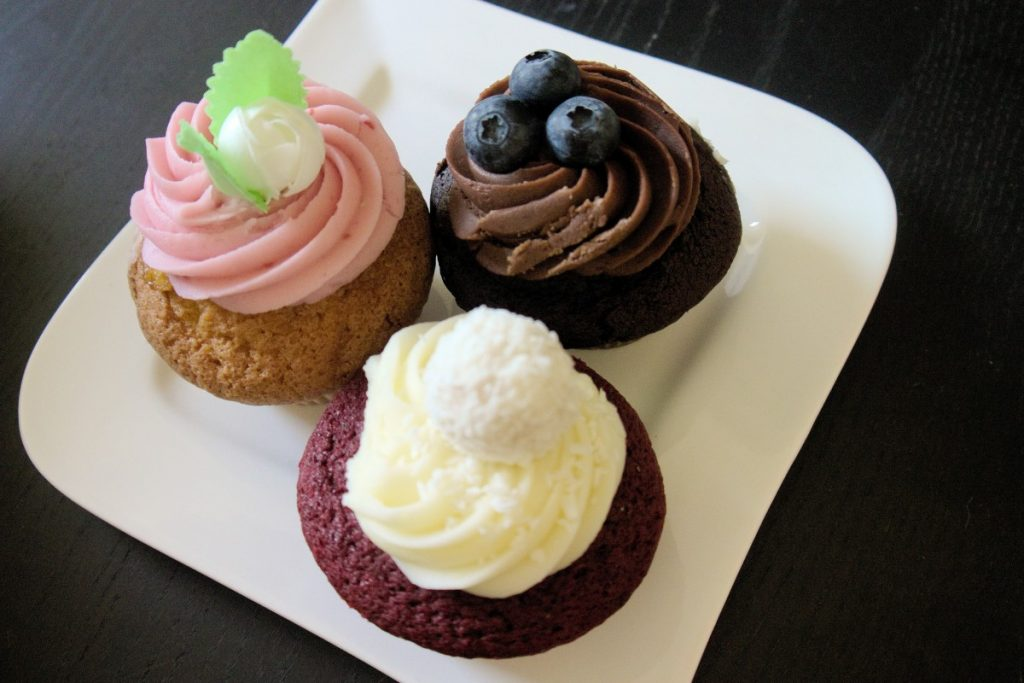 raspberry beret, chocolate lava and red velvet cupcakes with ornate decoration on a plate