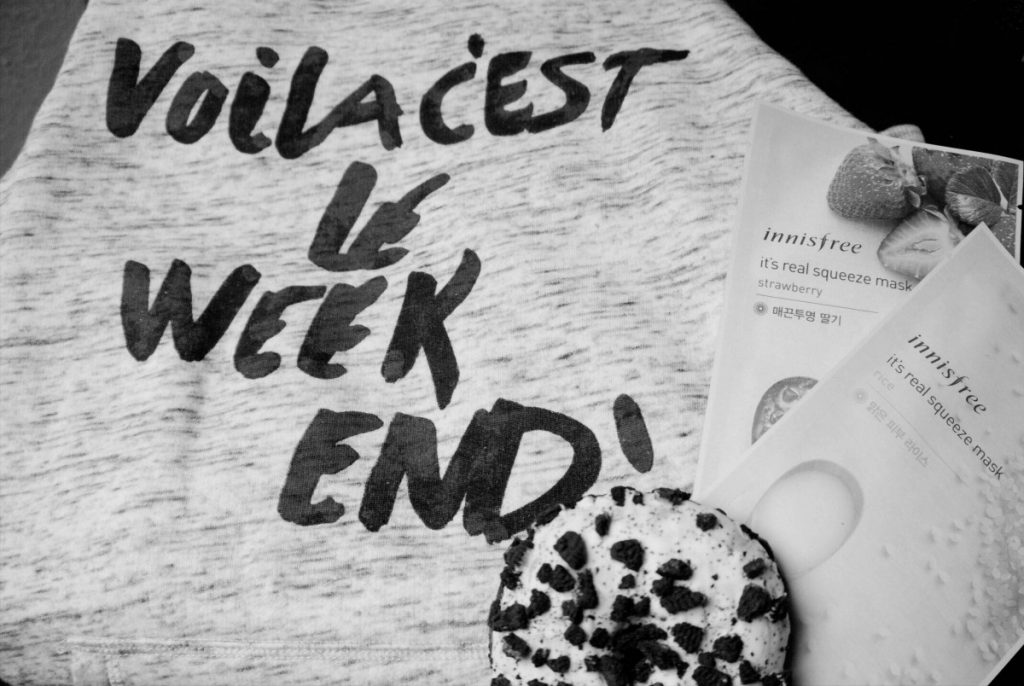 black and white image of sweater with voila c'est le weekend print, oreo donut and korean sheet masks by Innisfree in a flatlay