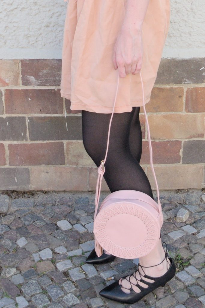 blush and black outfit with pink lyocell dress and round leather bag