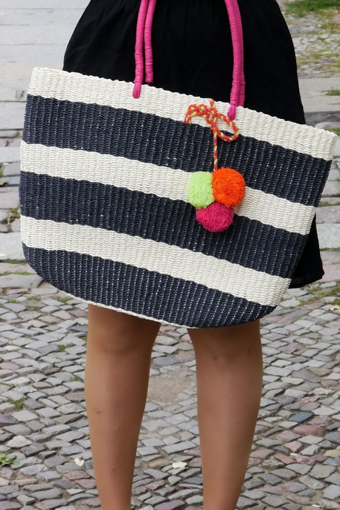 striped straw bag with fluo pom poms